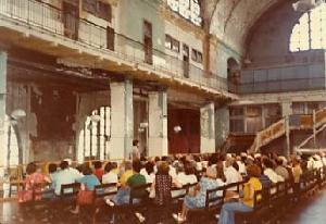 Bernardin addressing a tour in the unrestored Great Hall. Note damaged walls and old stairs and barriers in place from the post-immigration period.